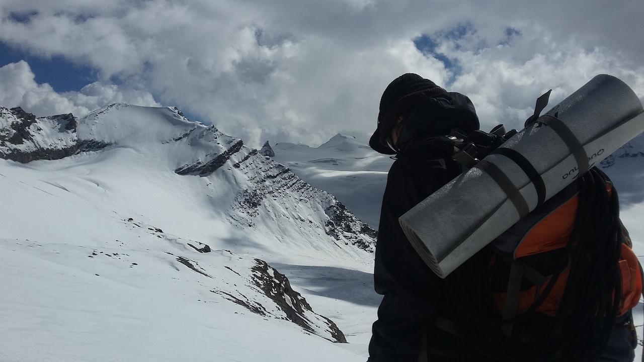 Trekker walking over snow capped mountain under cloudy sky