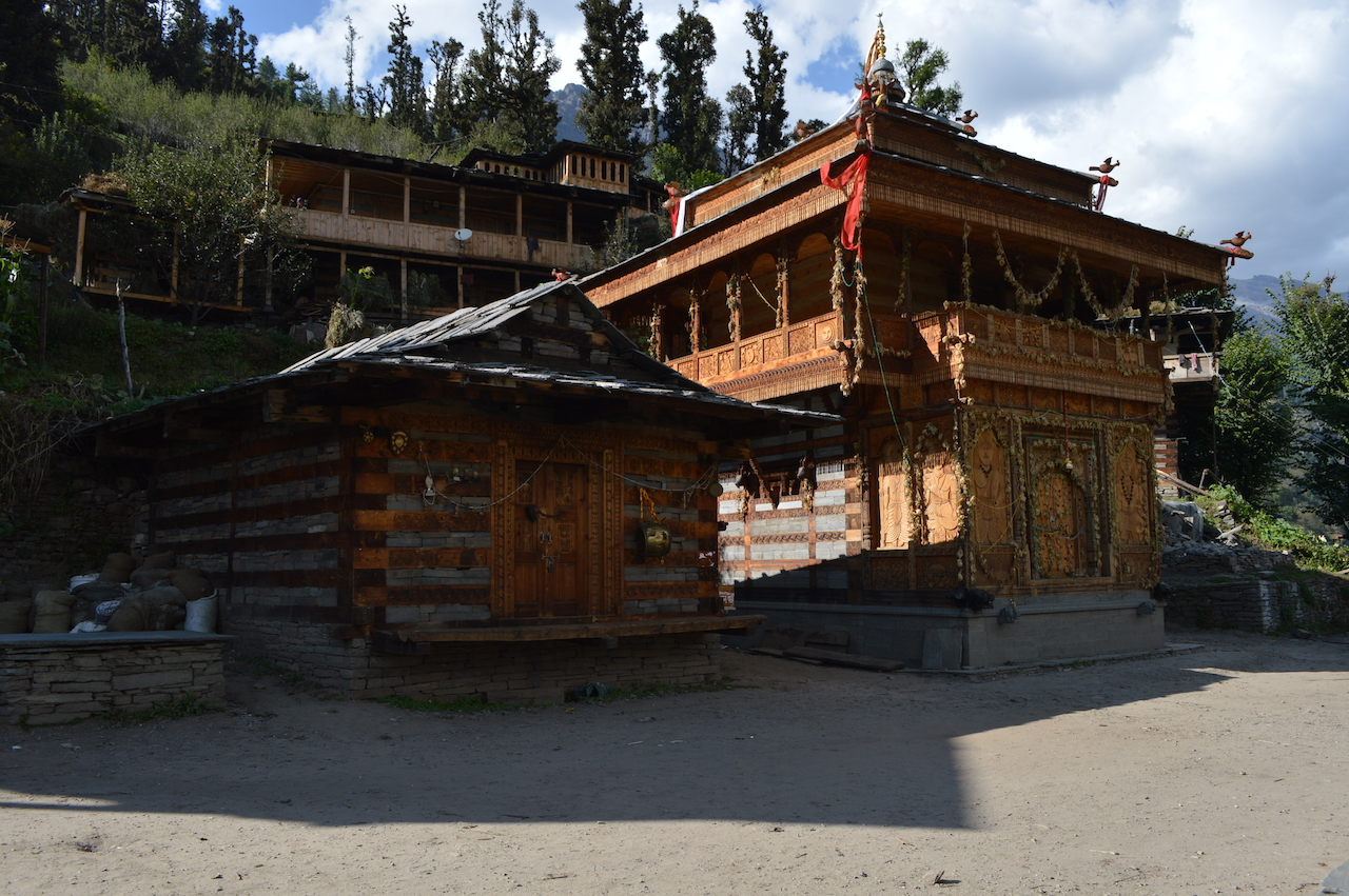 pokhu devta temple with brown colour paint shining with sunlight with green grass and trees