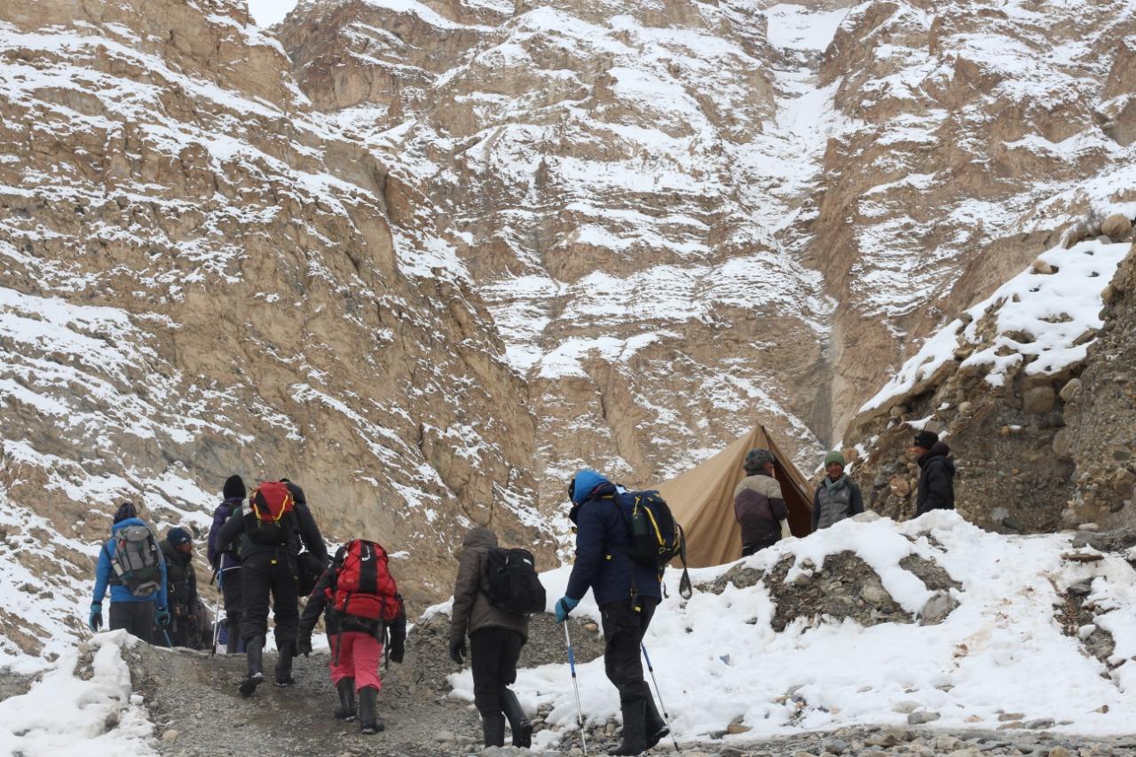 trekkers carrying trekking pole walking along campsite