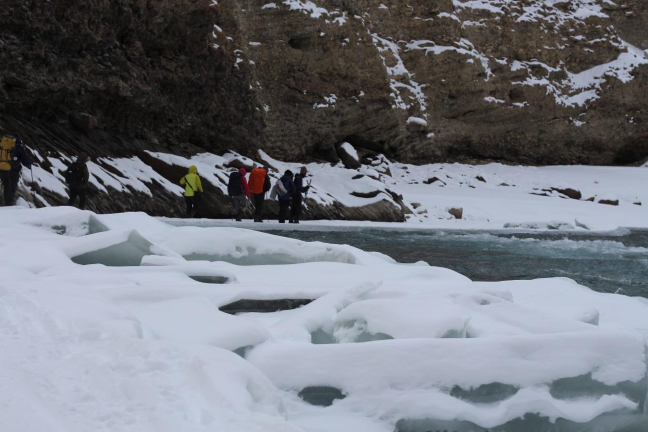 trekkers walking over the frozen chadar river enroute chadar trek
