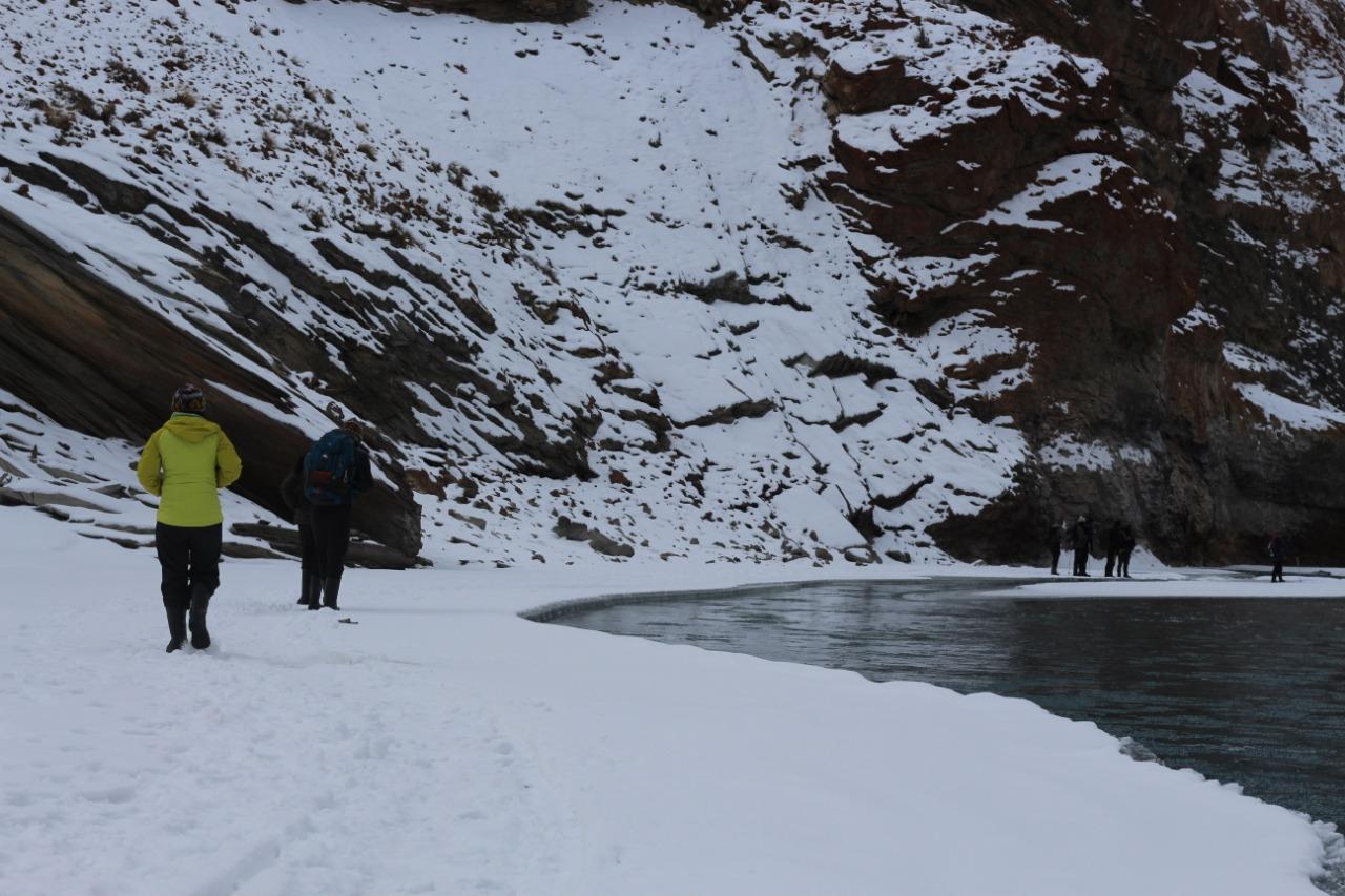 trekkers walking along the river enroute chadar trek