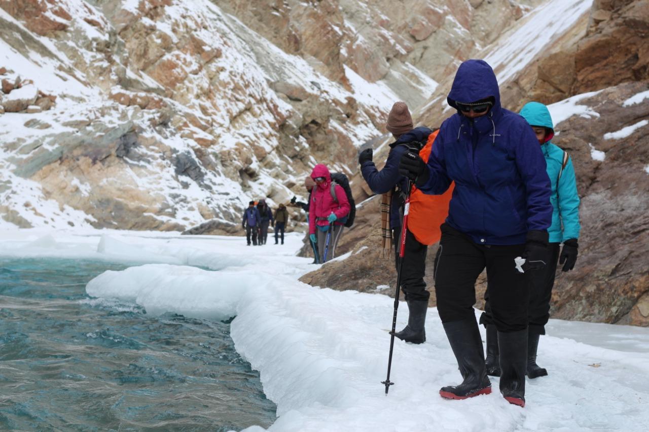 trekkers walking over the frozen chadar river holding trekking pole