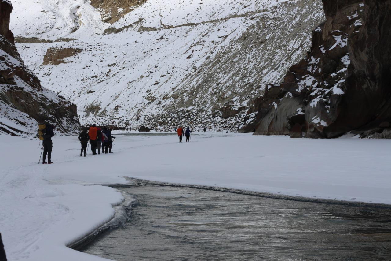 trekkers walking over frozen chadar river