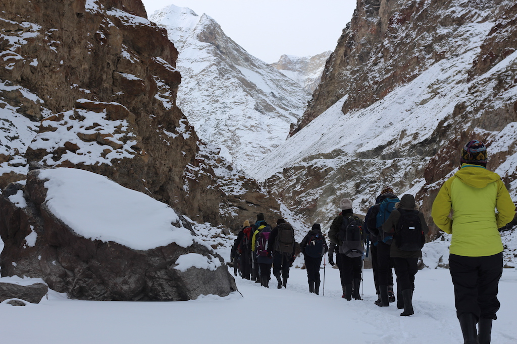 trekker walking in a sinle line, passing through the valley at chadar trek