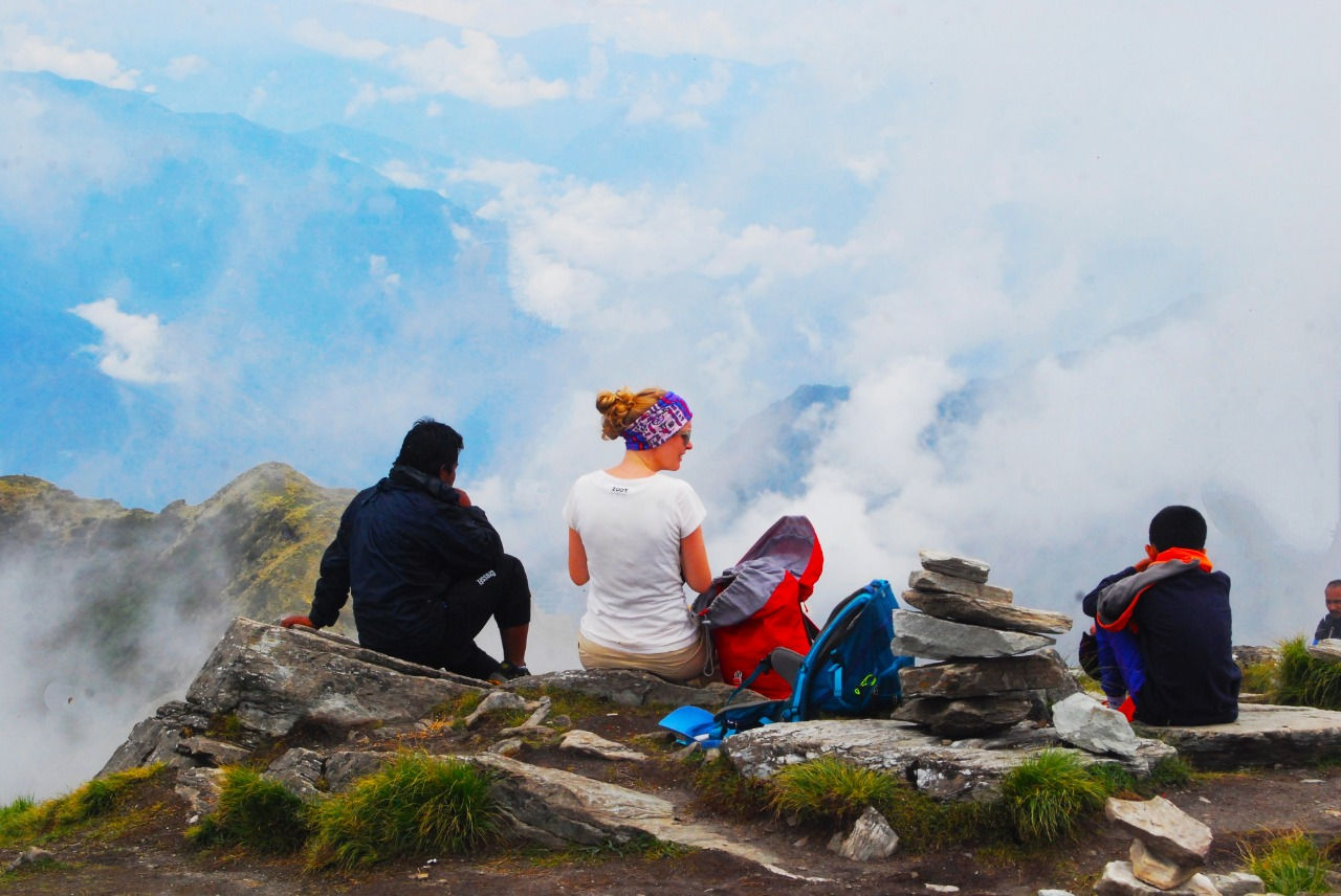 Trekkers resting at the chandrashila peak with stone placed on one another at right, glancing at the beautiful view of mist covering the   valley
