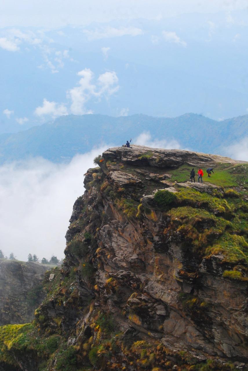 trekkers standing at cliff enroute chandrashila trek