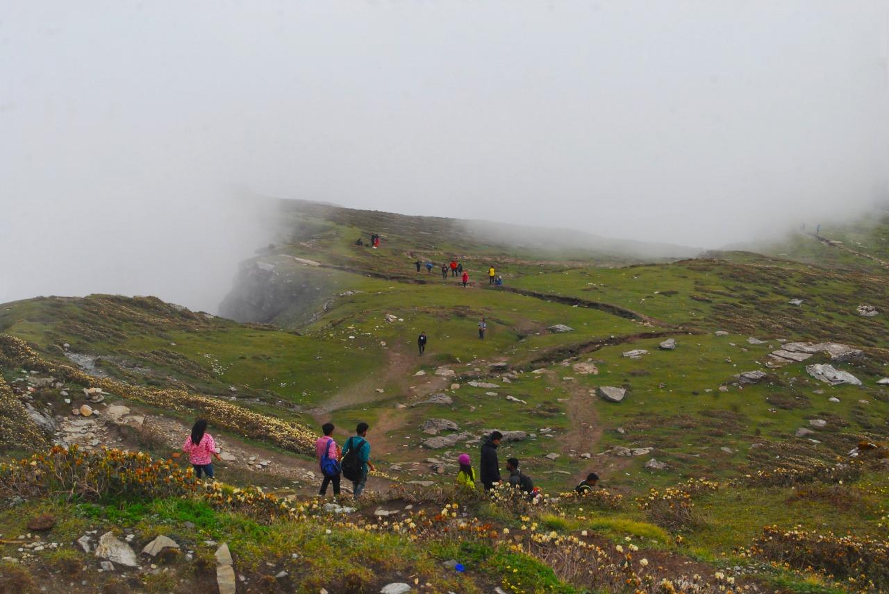 trekkers descending from chandrashila peak