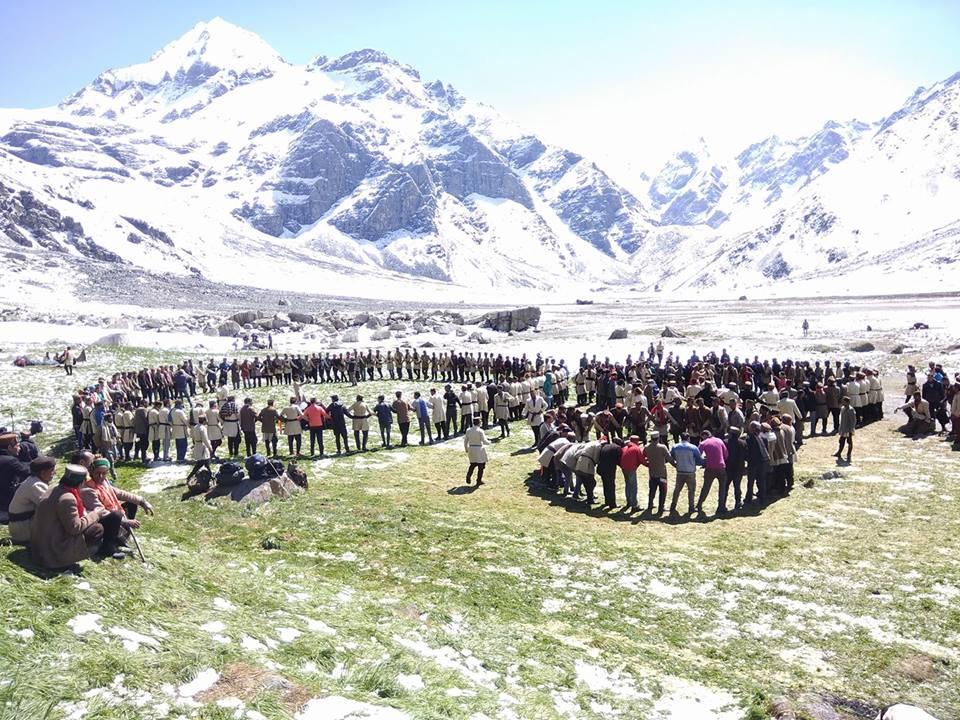 people hurdling around each other at devkyara trek with huge mountain massif on front