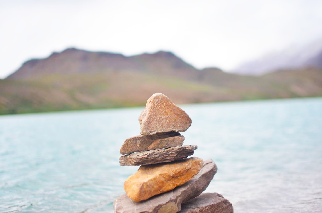 stone balancing on one another with blur image of chandratal lake and mountain slope on the back