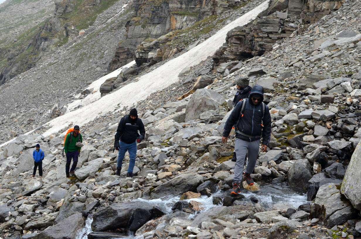 men crossing stream enroute hampta pass trek