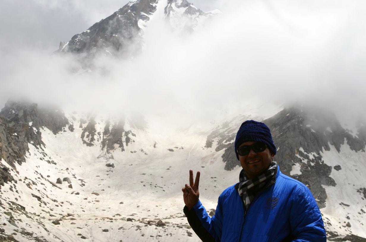 man wearing blue jacket standing in front of himalayan massif