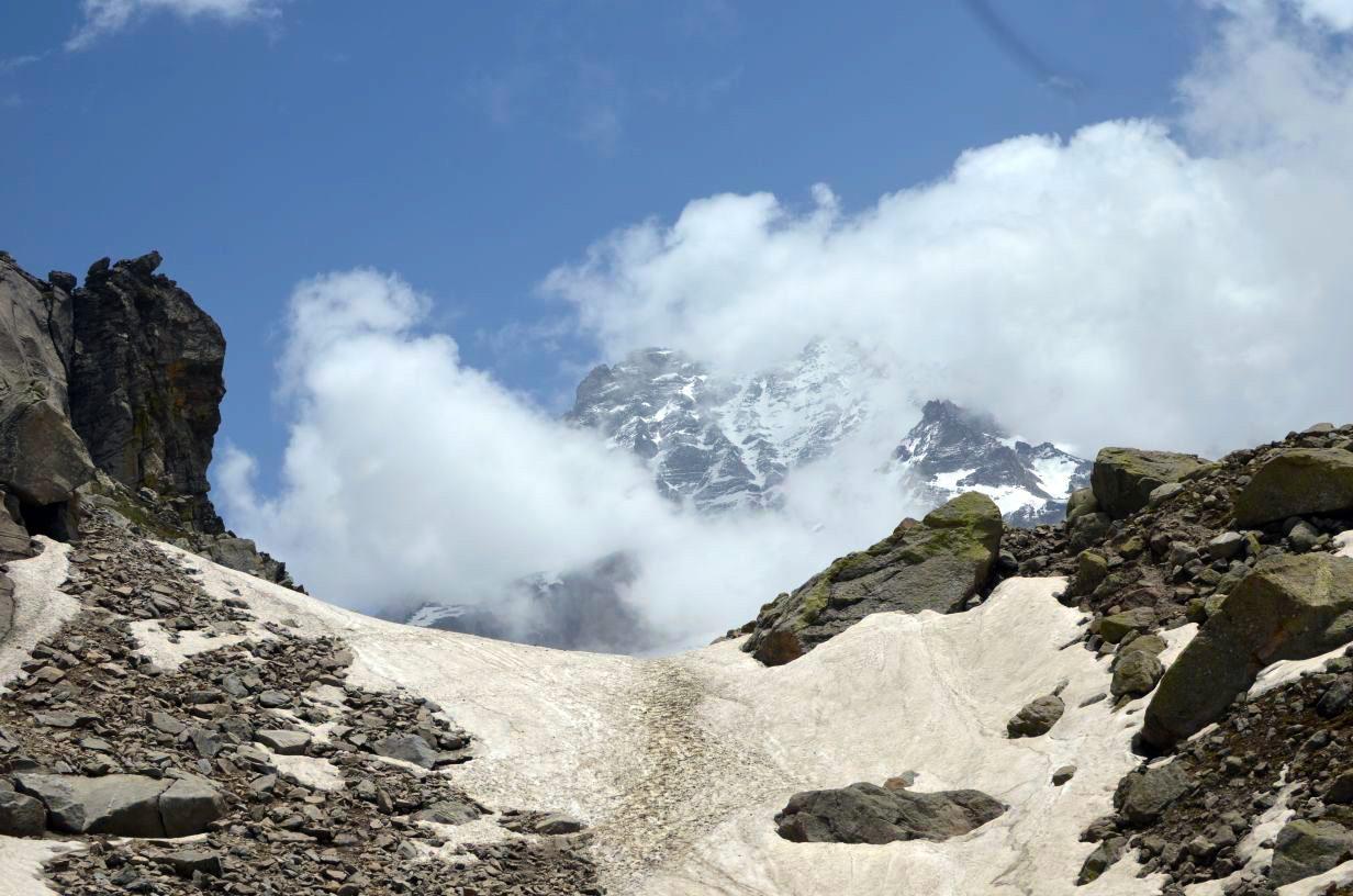 peak of himalayan massif visible through the fog enroute hampta pass