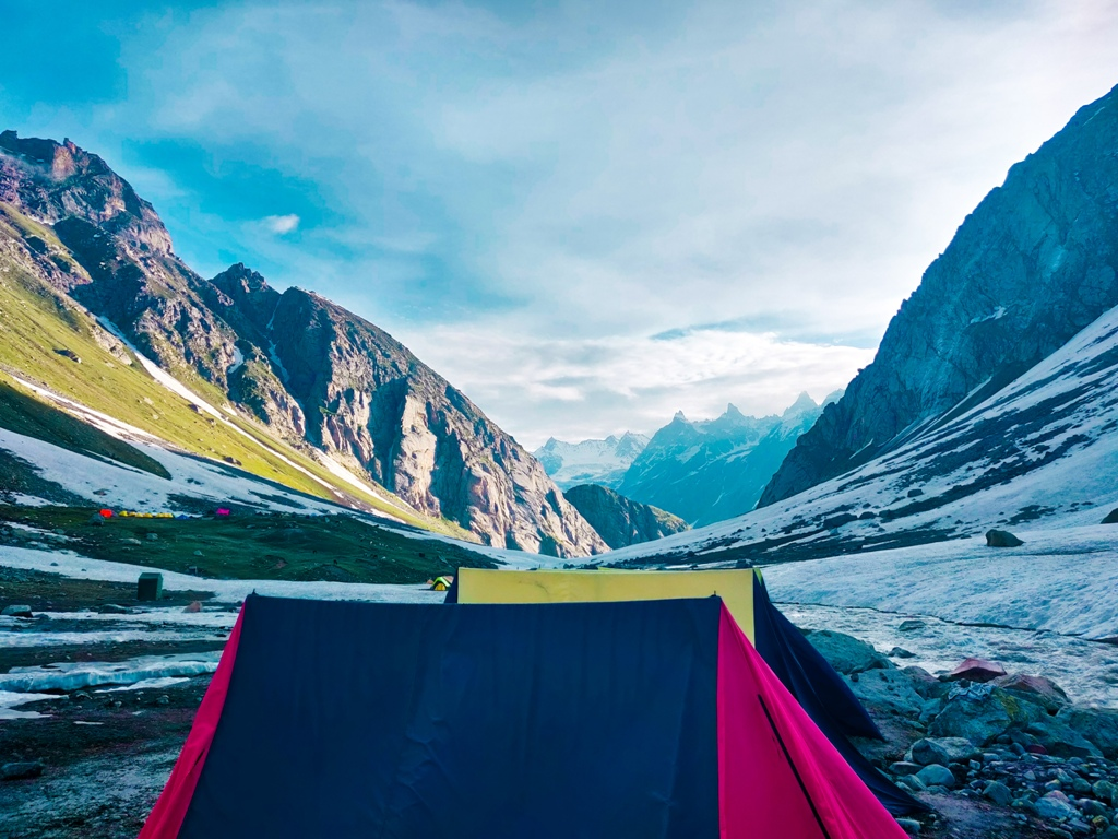 tent pitched in ground surrounded by huge mountains