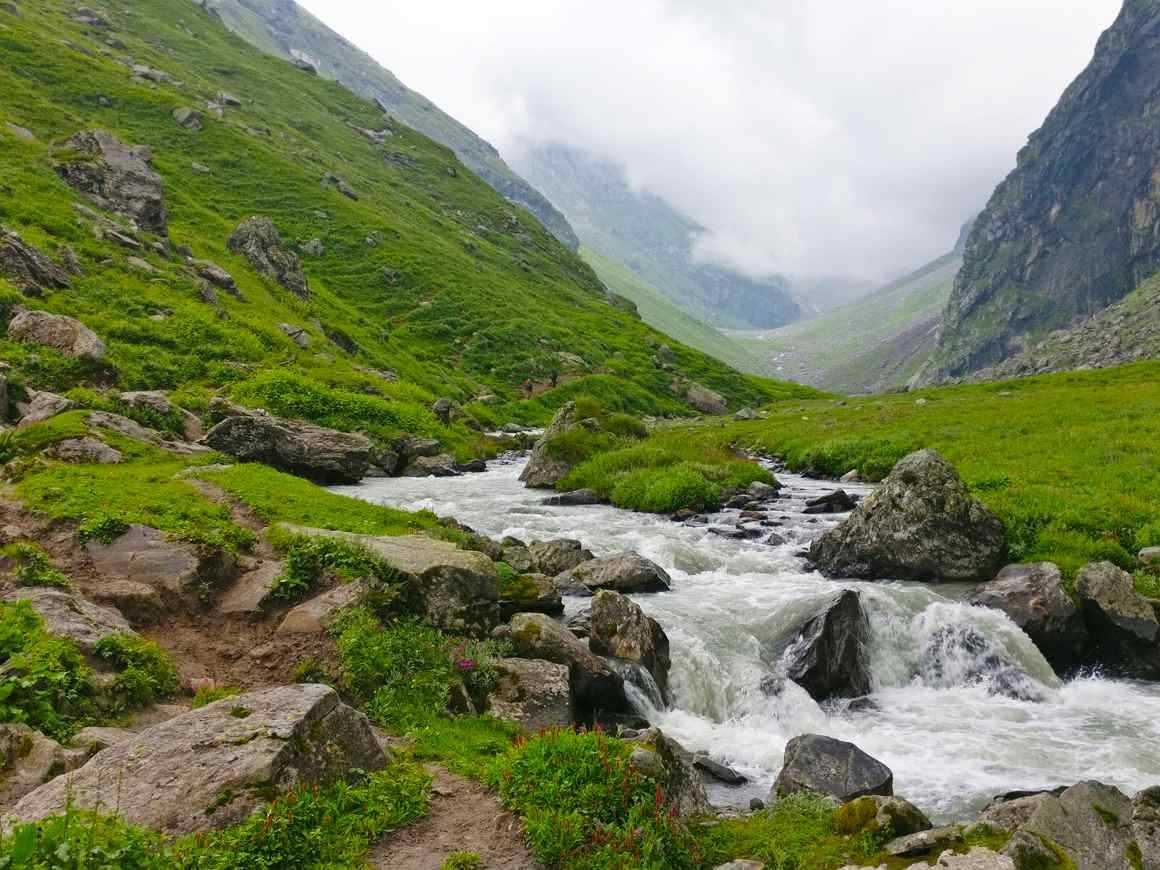 Supin river flowing through the valley in between huge mountains covered with green grass and grey fog filling the valley in back