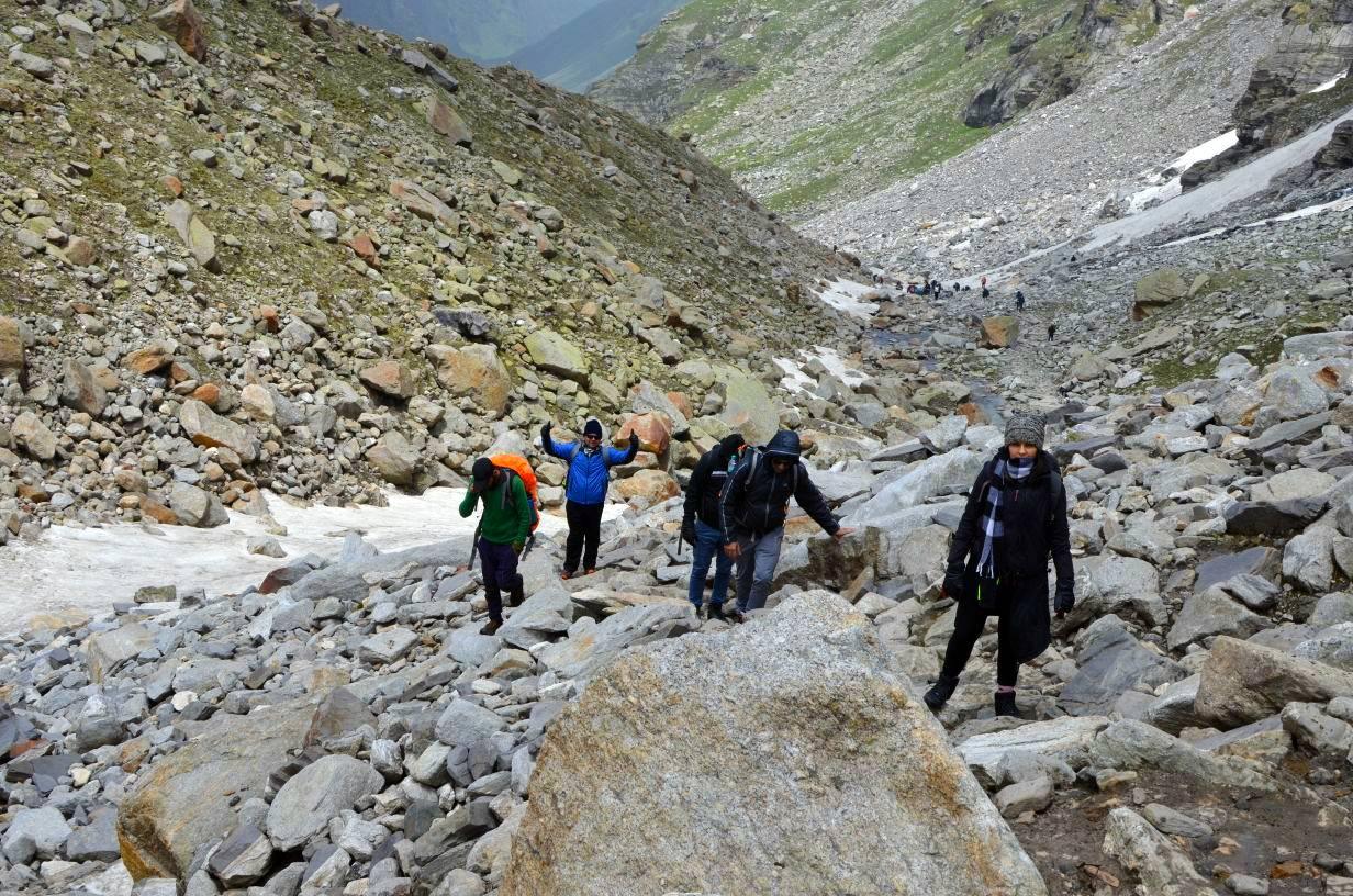 trekkers walking uphill through valley enroute hampta pass