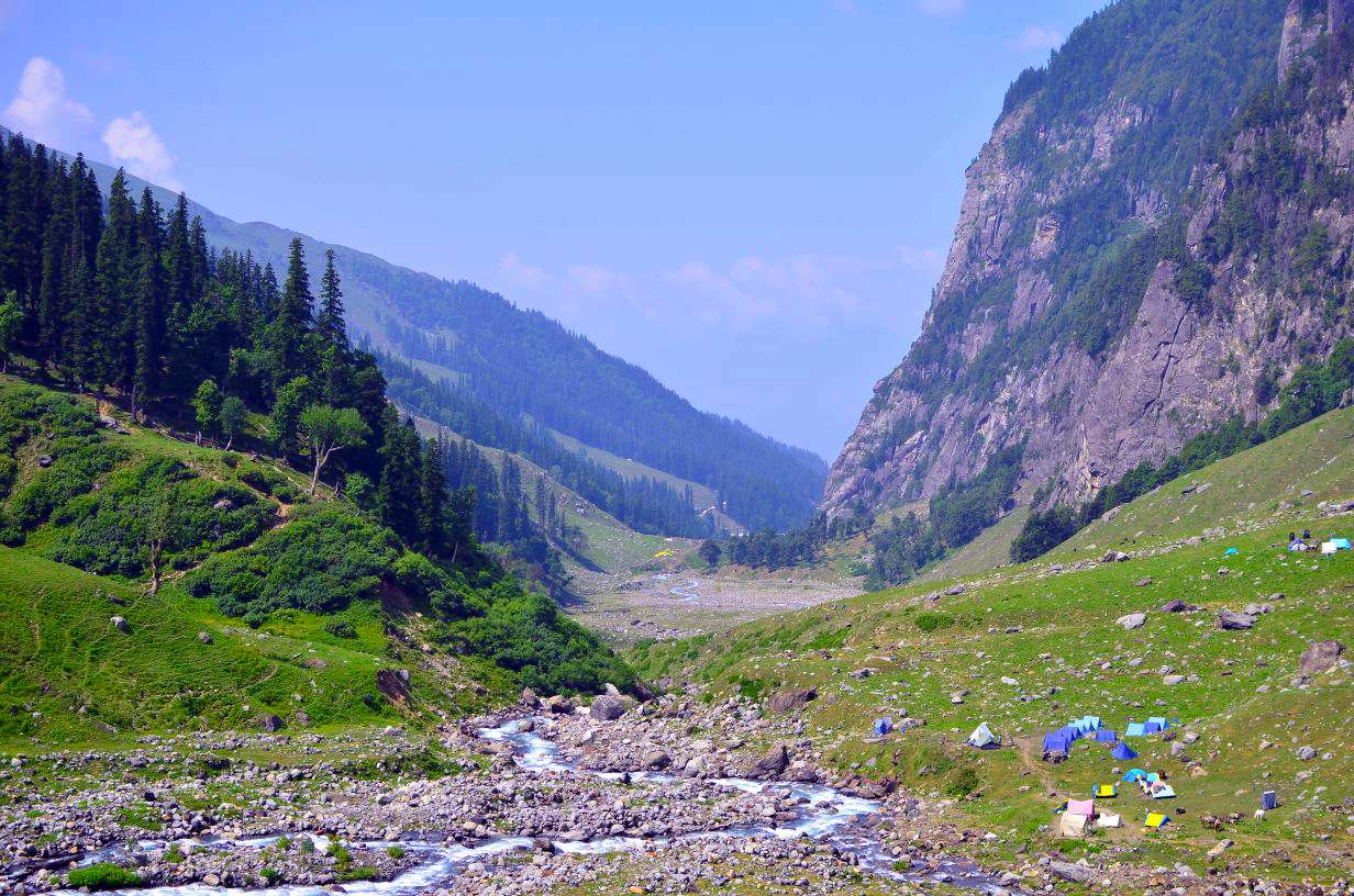 Supin river flowing in hampta pass valley with one side having greenery with thick forest of beautiful pine trees and with huge slope of rocks on the other all under the blue sky