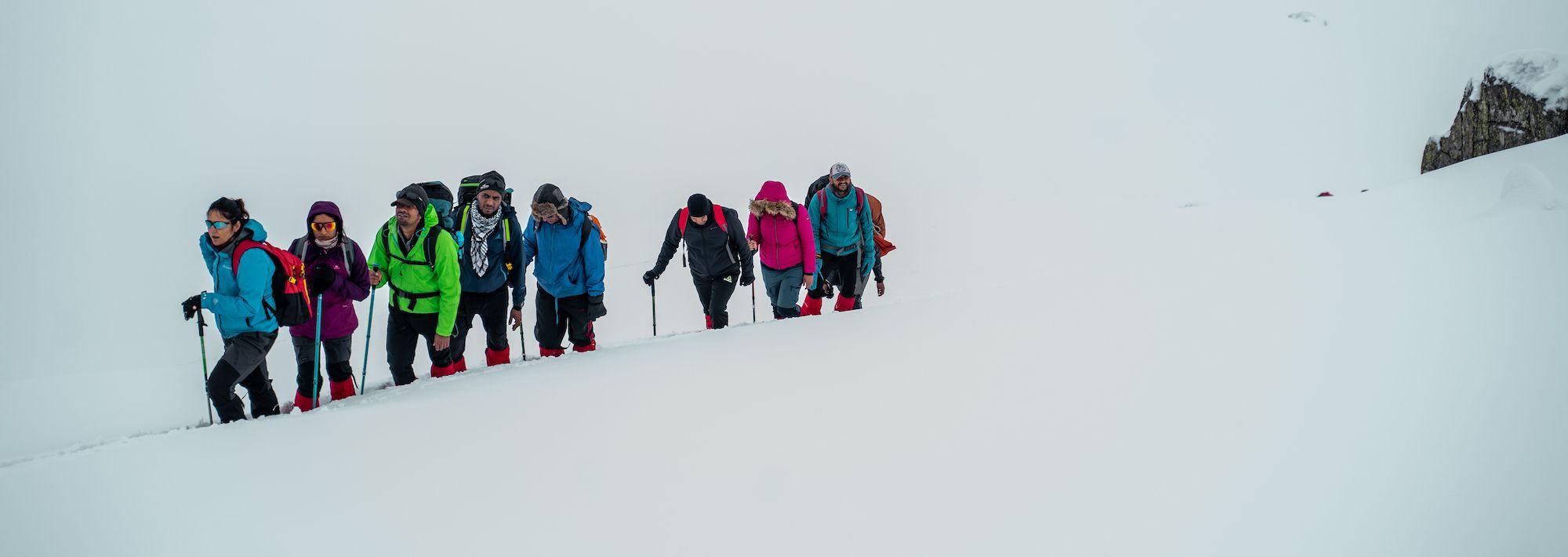 trek leader showing way to fellow trekker on kedarkantha trek