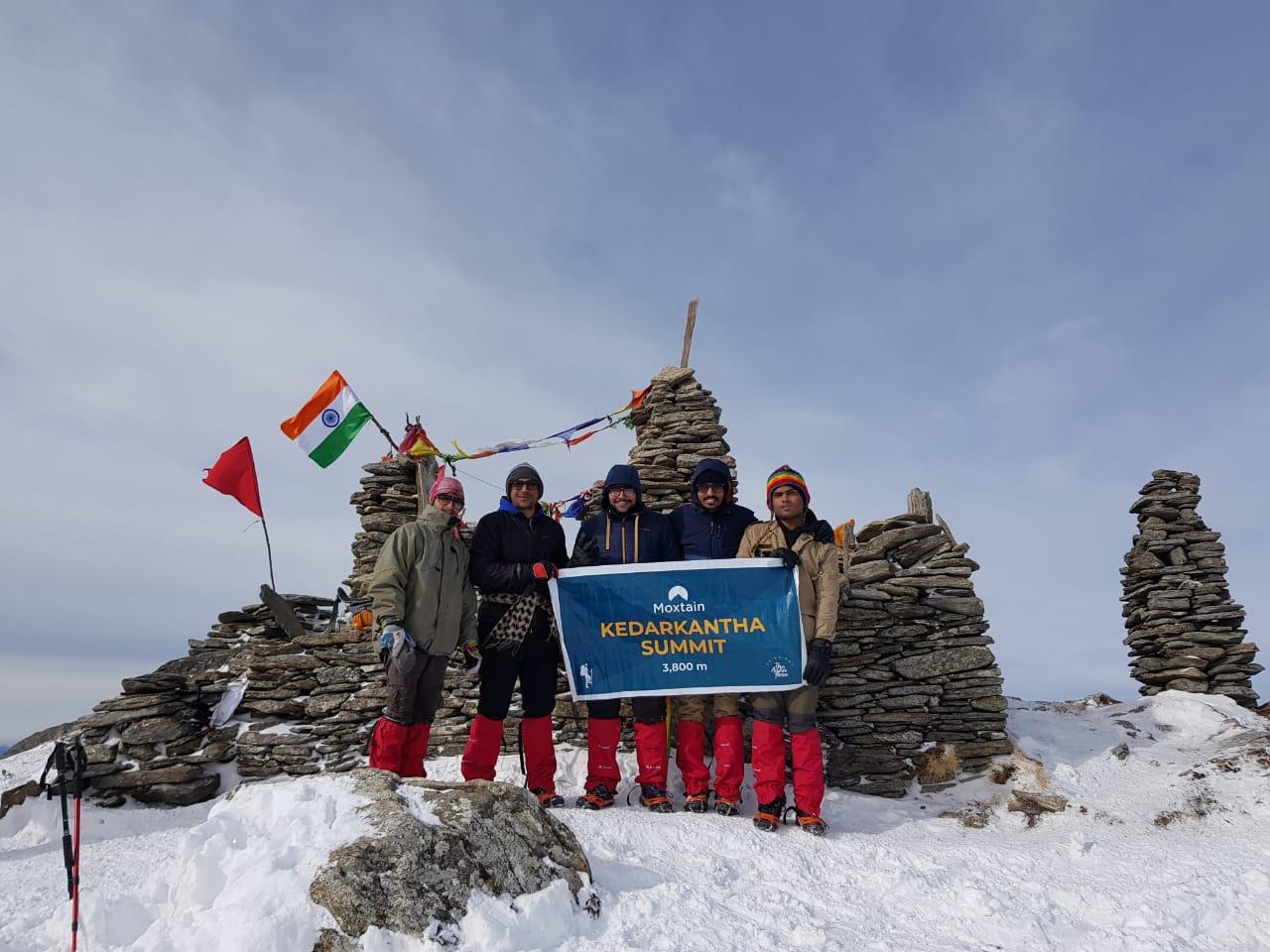 trekkers holding banner at kedarkantha summit