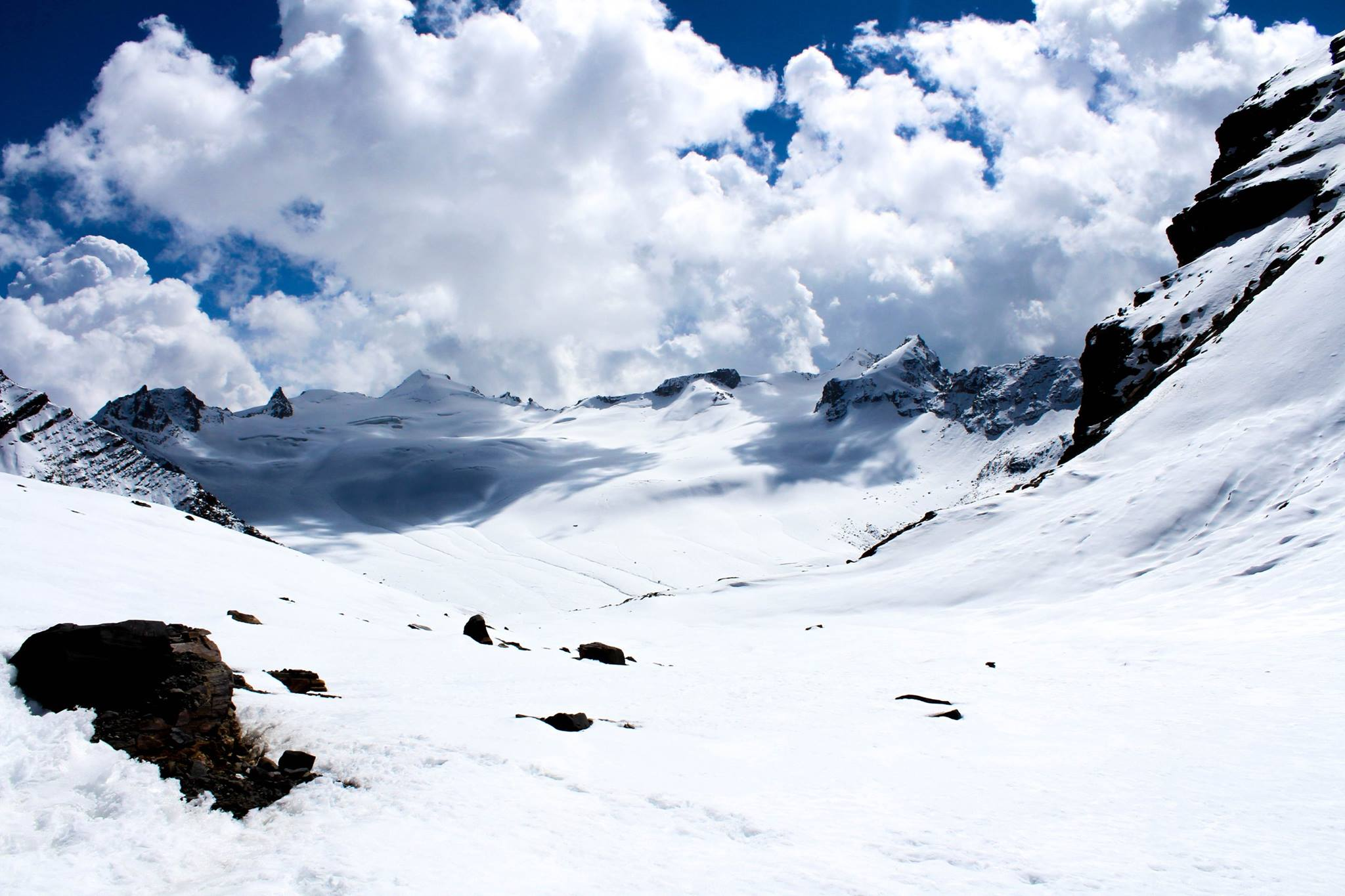 clouds hovereing over the snow covered mountains with bule sky, enroute pin valley