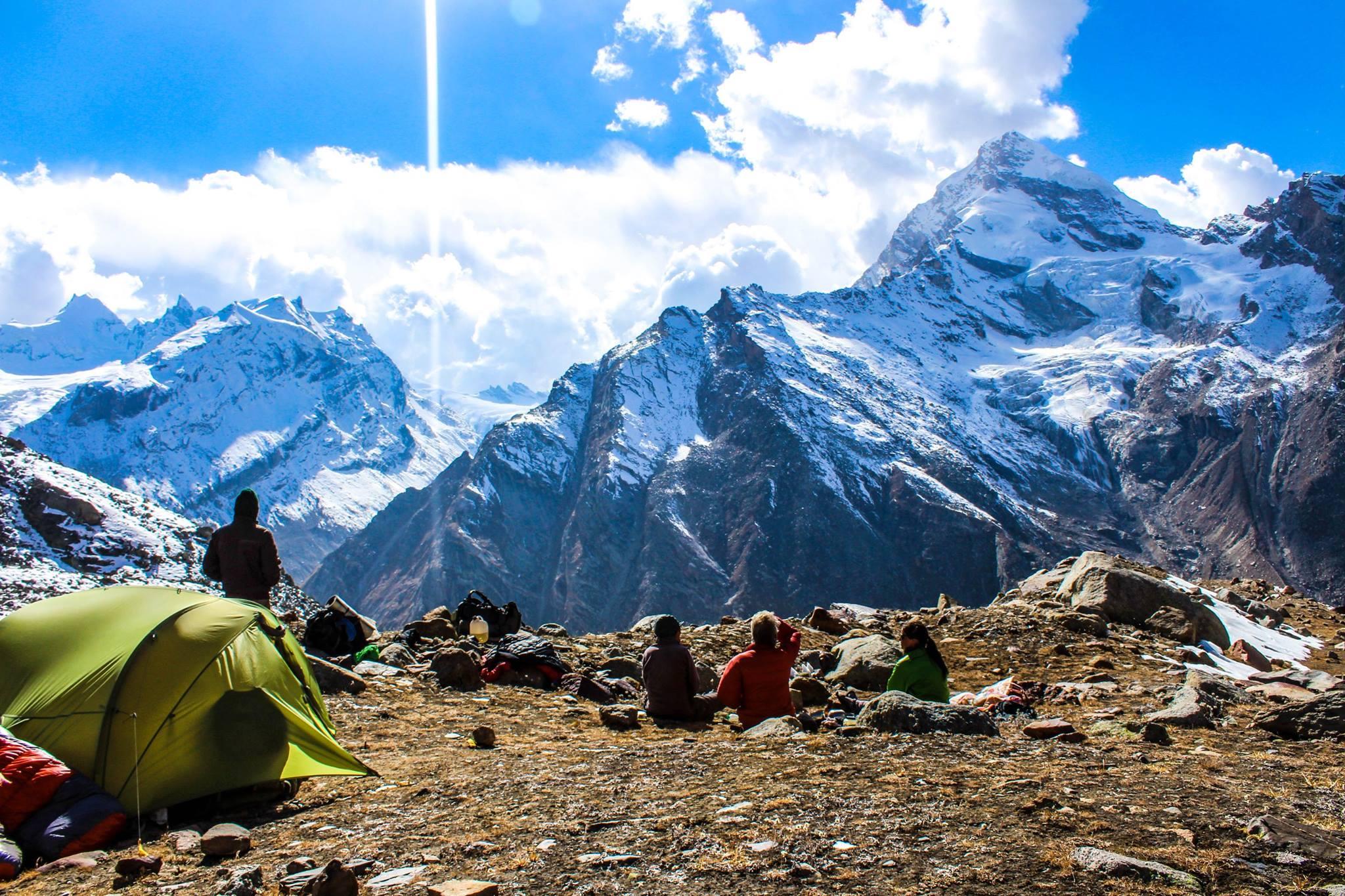 trekker resting at base camp in pin parvati pass trek lokking at the himalyan mountain ranges