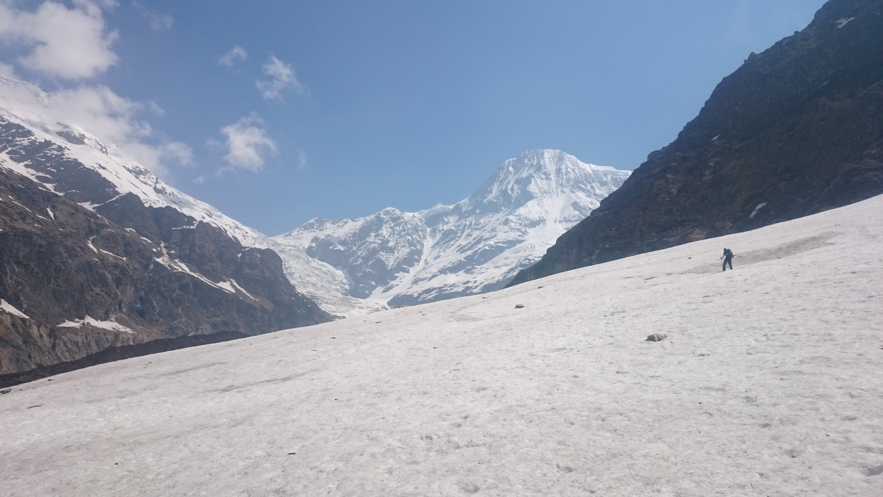 trekker walking on glacier with trekking stick and huge himalayan mountain massifs in front