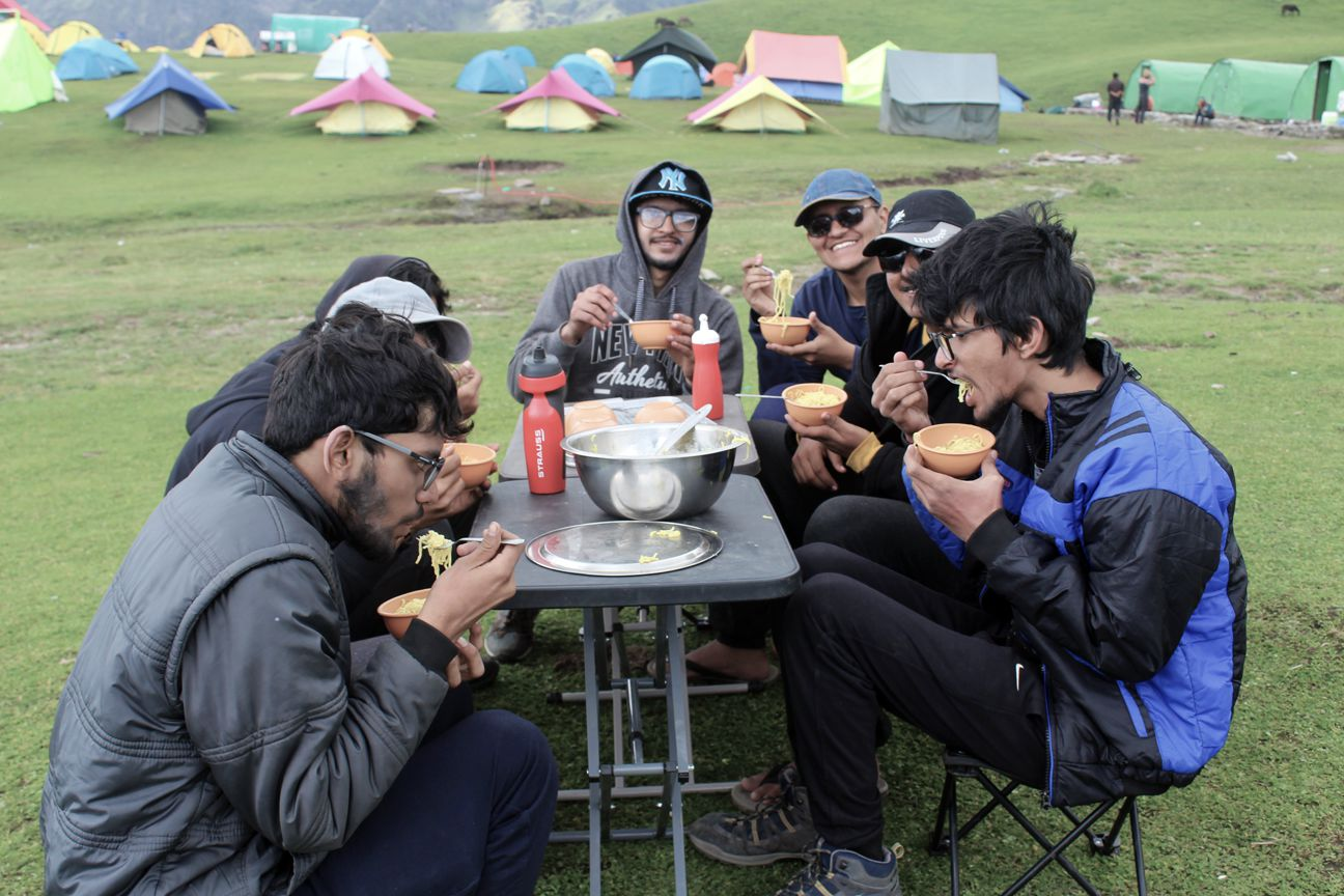 trekkers eating maggie with colourful tents pitched on backside at bedni bugyal campsite