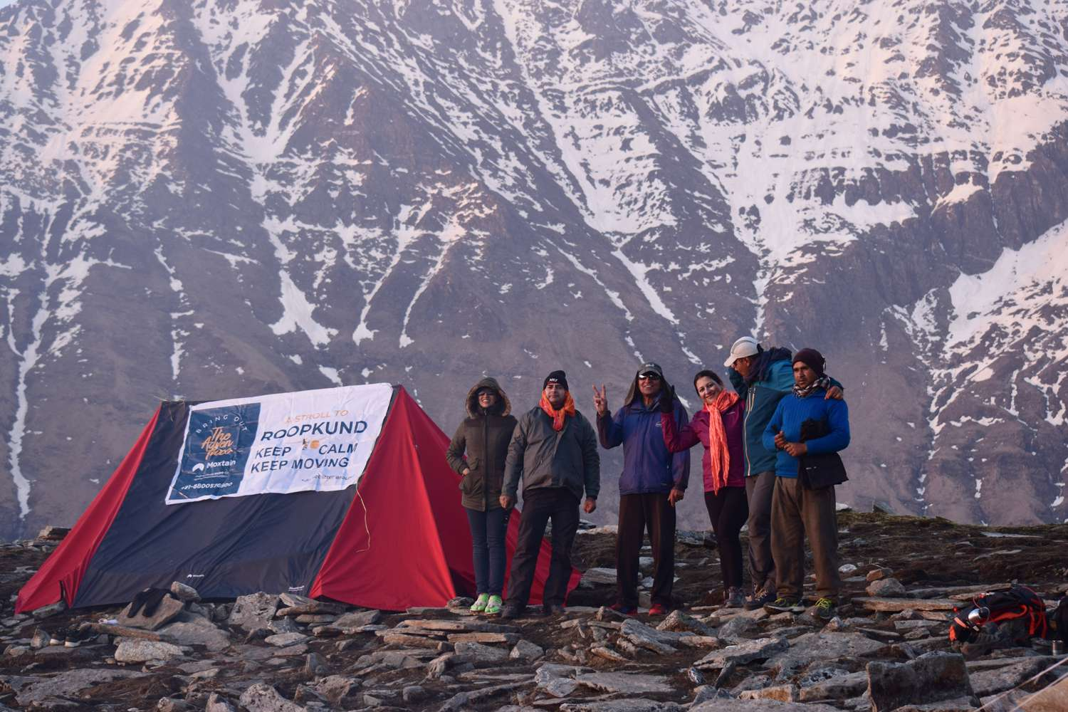 on the foot of huge himalayan mountain trekkers standing near tent