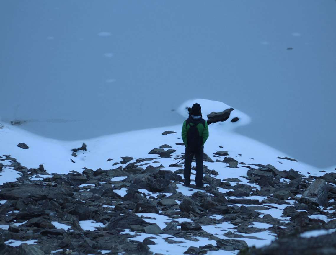 man wearing green jacket watching the frozen roopkund lake