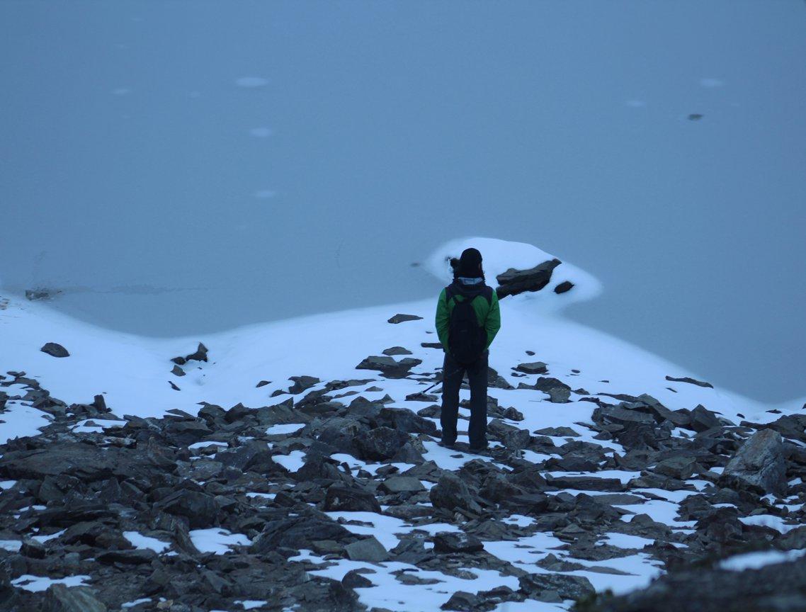 man wearing green jacket watching the frozen roopkund lake