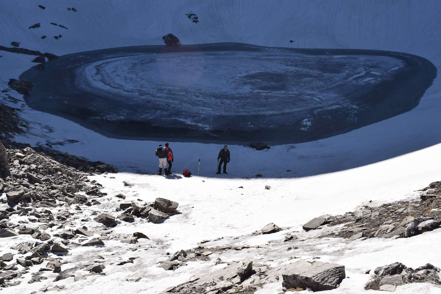 roopkund lake with white patch of snow in the middle