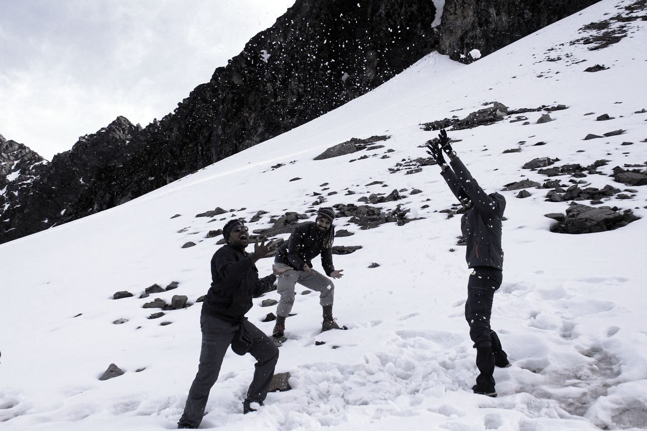 people playing with snow on a snow covered himalyan mountain